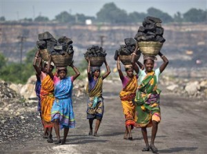 Local women carry coal taken from open cast coal field at Dhanbad district in Jharkhand